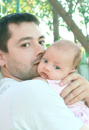 Handsome father holding beautiful little baby girl outdoor near the tree photo
