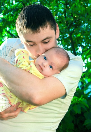 Handsome father kissing little beautiful baby girl on nature green background and babe looking in camera with serious sight photo