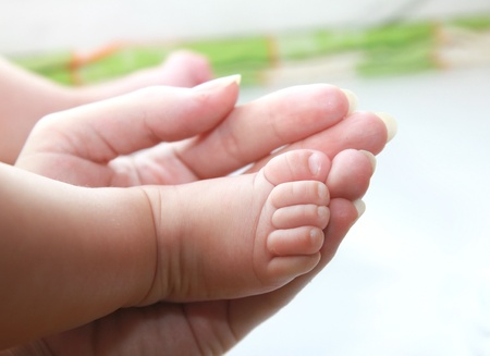 pregnancy: Closeup hand of mother holding small baby girl foot Stock Photo