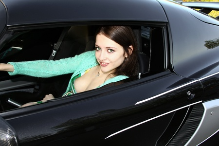 Beautiful young smiling woman looking from opened window of sport car photo