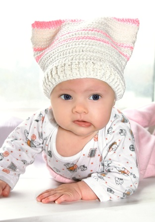 Portrait of funny baby girl in big hat and bright blue eyes photo