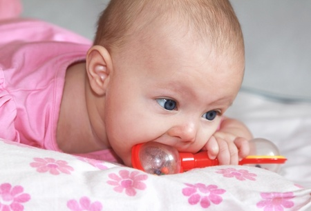 suck: Closeup portrait of beautiful baby girl sucking the toy and joy