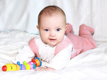 Beautiful smiling baby girl lying and playing with toy and looking in camera photo