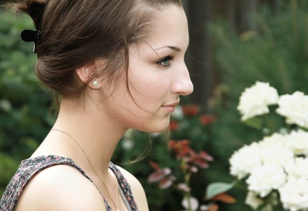 ennui: Beautiful sad thinking teen girl on nature flowers background is looking Stock Photo