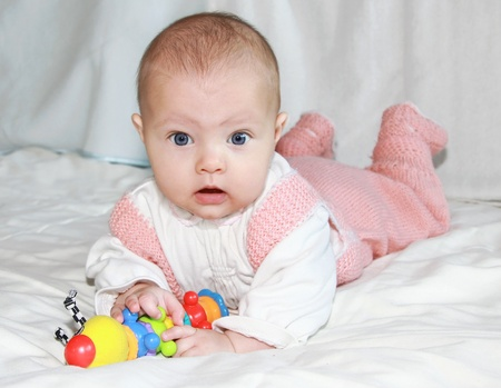 Surprised beautiful baby girl playing with colorful toy photo