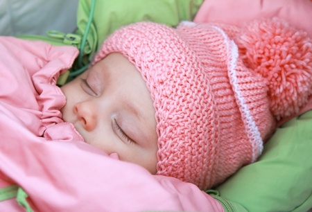 Sleeping beautiful newborn baby girl in pink hat outdoor in winter cold weather Stock Photo