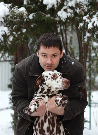 Happy young man holding Dalmatian dog on the hands on winter nature background near the trees with snow photo