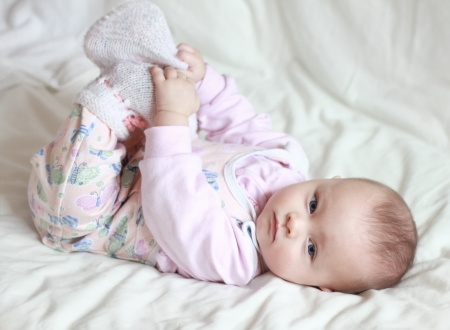 pie bebe: Hermosa ni�a peque�a beb� acostado sobre la espalda y los pies sosteniendo ella misma. Beb� con mirada seria y ojos azules.