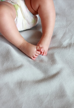 Beautiful small baby girl feet on blue cover photo