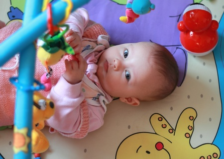 developmental: Beautiful girl playing with toys on developmental mat. Small baby looking with interest in camera Stock Photo