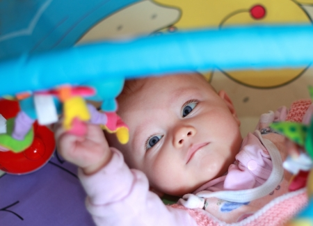 Closeup portrait of beautiful girl with bright blue eyes playing in developmental mat Stock Photo