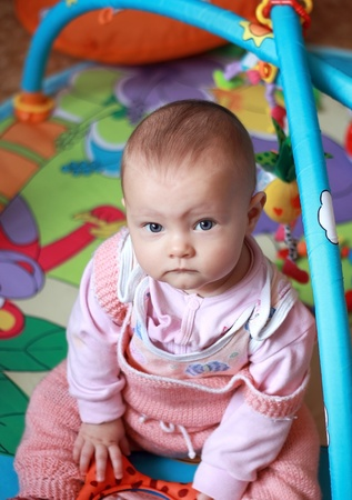 Adorable baby girl sitting and playing in developmental mat. She serious looking in camera. Stock Photo - 12074743
