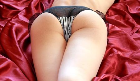 Seksualne gorące pośladki kobiety leżącej na jasnoczerwony arkusz na łóżku w seksownej bieliźnie