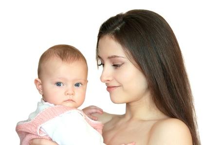 madre y bebe: La madre y bella mujer con ternura y el amor mirando a su niña y el niño mirando a puerta cerrada. Primer retrato aislado en fondo blanco