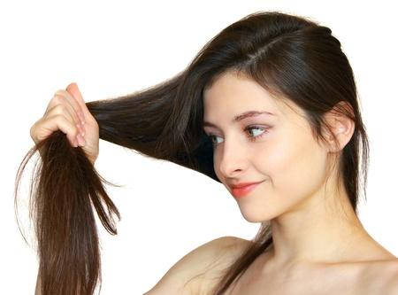 belle brunette: Closeup portrait d'une jeune fille belle tenue des cheveux sains dans la main et en regardant à sa isolé sur fond blanc