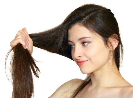 beautiful brunette: Closeup portrait of beautiful girl holding healthy hair in the hand and looking at its isolated on white background Stock Photo