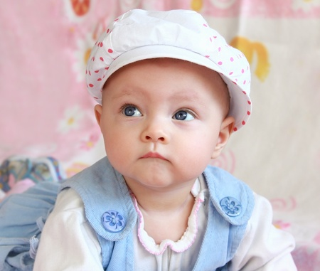 Closeup portrait of adorable baby girl in cap with thoughtful blue eyes photo