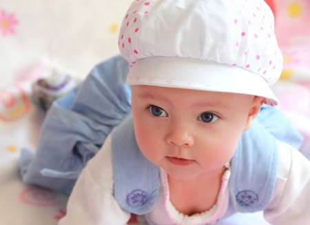 Closeup portrait of adorable baby girl in cap with blue eyes lying