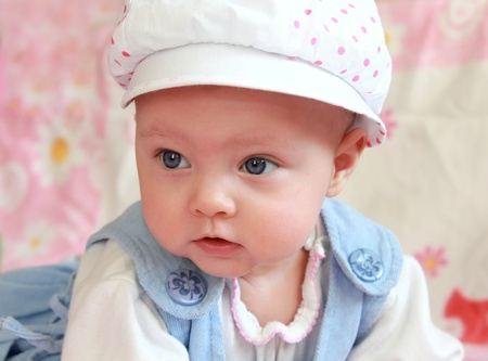 Closeup portrait of adorable baby girl in cap with blue eyes looking with interest photo