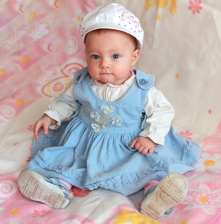 Adorable baby girl sitting in beautiful blue dress and funny hat photo