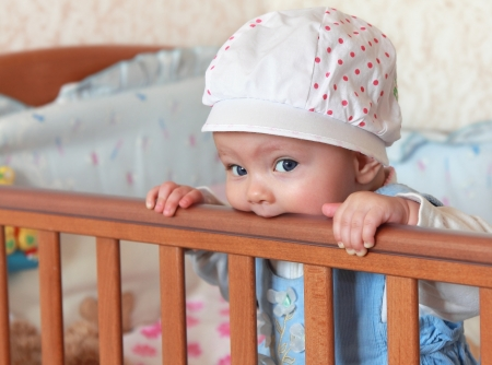 Funny baby girl in hat standing and biting the bed and looking Stock Photo