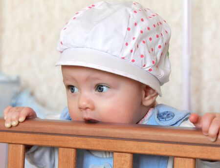 Closeup portrait of funny baby girl in hat standing and biting the bed photo