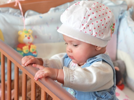 Adorable baby girl standing in bed in beautiful cap in bedroom with toys. Rest time photo