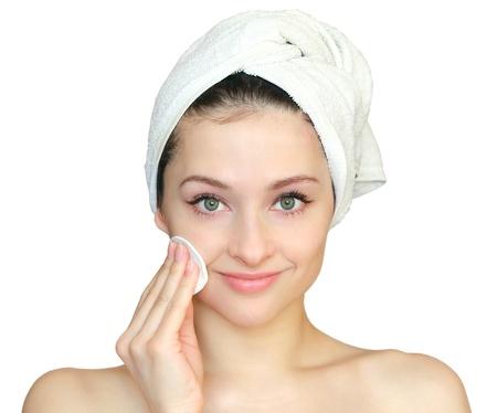 gezicht: Mooie jonge vrouw het reinigen van tampon de huid op het gezicht na bad in handdoek op de hand op een witte achtergrond. Close-up portret