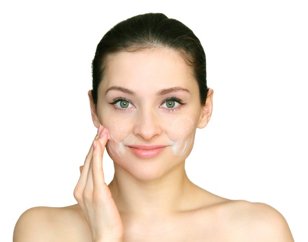 Young beautiful woman applying the cleansing foam on the face skin the hand isolated on white background. photo