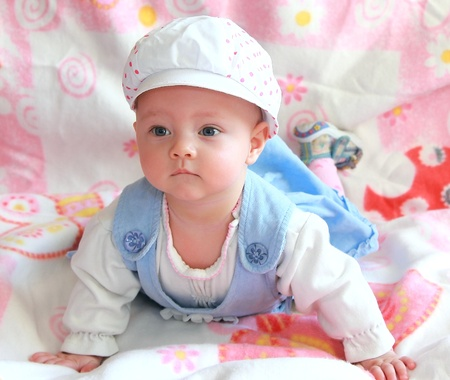 Beautiful baby girl in funny cap and blue dress lying and looking with interest photo