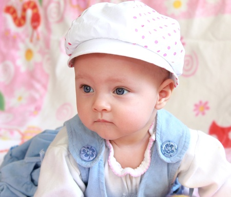 Portrait of beautiful baby girl in funny hat looking serious photo