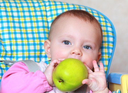Closeup portrait of beautiful baby girl eating big green apple sitting on chair Stock Photo - 12361834