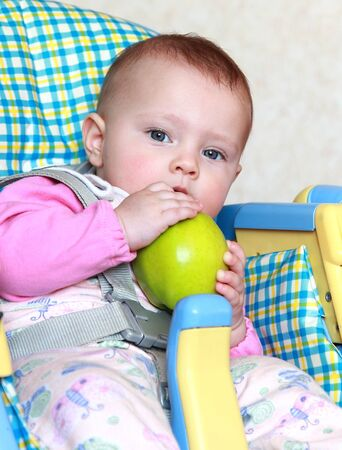 Portrait of beautiful baby girl eating big green apple sitting on chair and looking in camera Stock Photo - 12361833