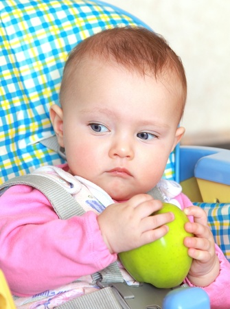 Closeup colorful portrait of beautiful baby girl holding green apple and serious looking down Stock Photo - 12361836