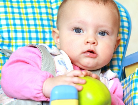 Closeup portrait of baby girl holding green apple sitting on chair Stock Photo - 12361841
