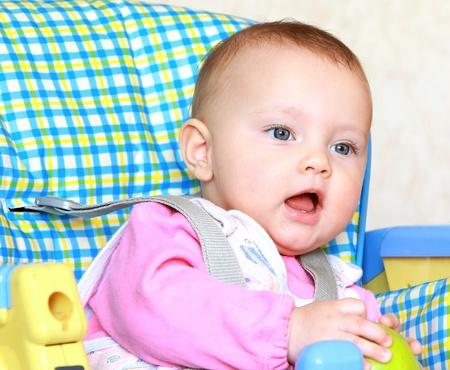Adorable funny baby girl with opened mouth holding green apple sitting in the chair Stock Photo - 12361839