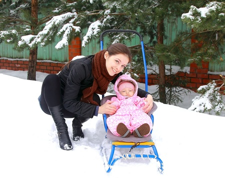 Beautiful happy young mother with small baby girl walking in sledge on snow on winter cold weather