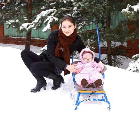 trineo: Hermosa madre joven feliz con niña pequeña caminando en trineo sobre la nieve en el frío invierno