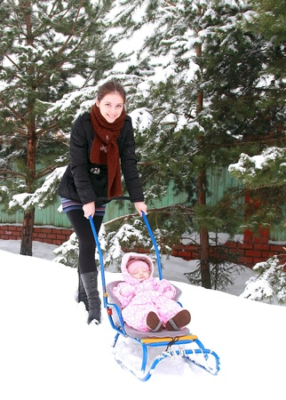 Beautiful happy young mother walking with small baby girl sitting in sledge on winter cold weather with much snow near the fir tree photo