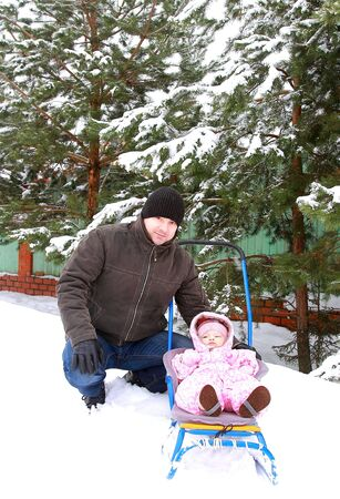 Handsome father sitting with baby girl on snow sleigh on winter nature background near the beautiful fir trees photo