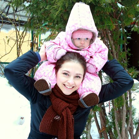 Portrait of little baby sitting on smiling mother shoulders near the fit trees on winter snow weather photo