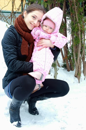 Beautiful young mother holding little baby girl on winter background. Portrait of happy family photo