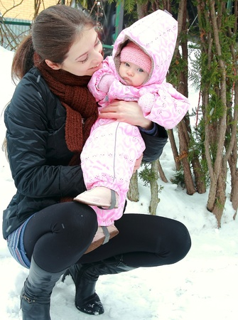 Beautiful yong mother looking at her little baby girl with love on winter background near the firs photo