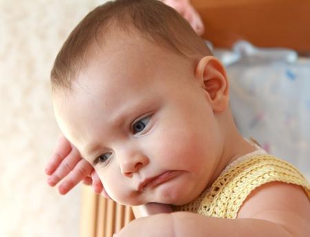 m�lancolie: Belle fille debout m�lancolie b�b� dans le lit le long. Closeup portrait