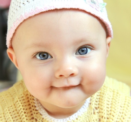 Closeup portrait of funny baby girl with blue big eyes in hat photo