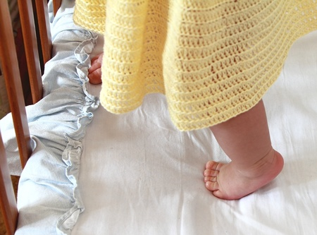 Beautiful small baby girl foot standing in bed photo