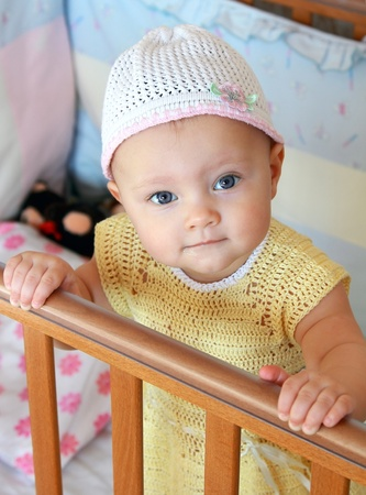 Portrait of beautiful baby girl in hat standing in bed and looking in camera with smiling holding the wooden bed photo