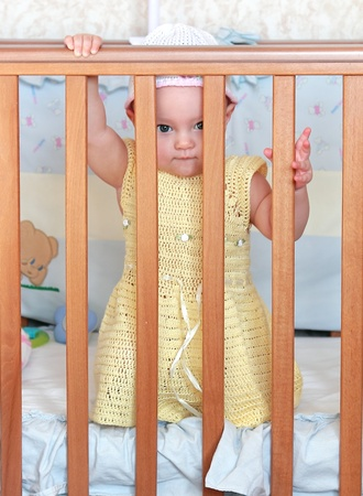 Beautiful baby girl in yellow dress peeping out of wooden safety bed  photo