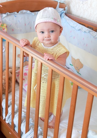 Beautiful angelic baby girl in yellow dress standing in bed and looking at camera photo