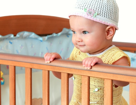 Beautiful smiling baby girl in hat standing in wooden bed isolated photo